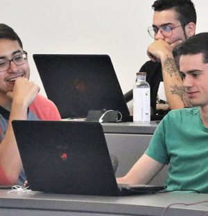 three male students working together in a classroom with their laptops
