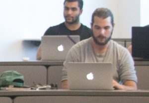 two male students working on their Apple laptops